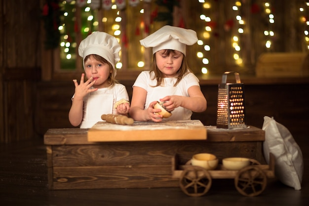 Le sorelle dei bambini cucinano con un mattarello per allungare il concetto di infanzia,