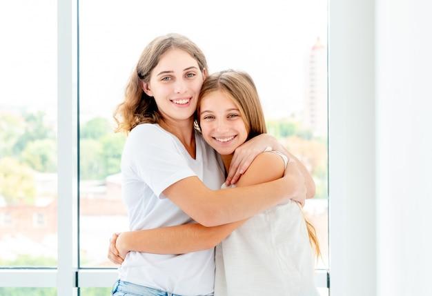 Le sorelle si abbracciano felici nella stanza luminosa