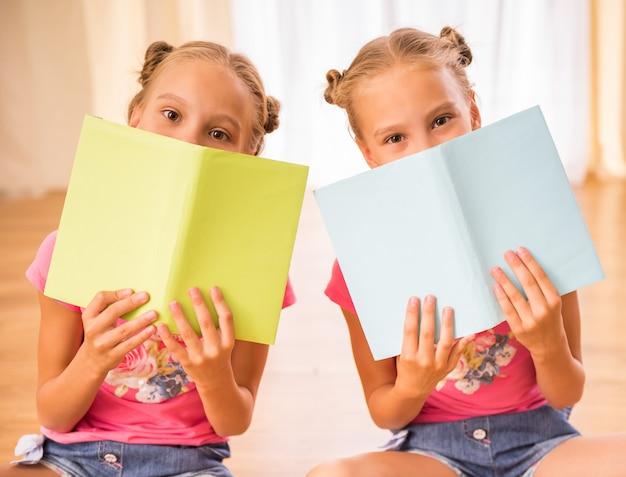 Le sorelle si divertono mentre leggono libri seduti sul pavimento.