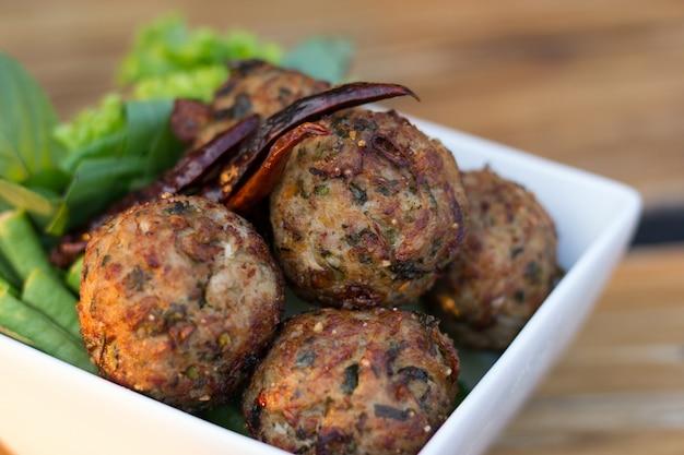 Le spezie piccanti tritano le palle di maiale con insalata in un piatto bianco sul tavolo. cibo tailandese (larb moo tod)