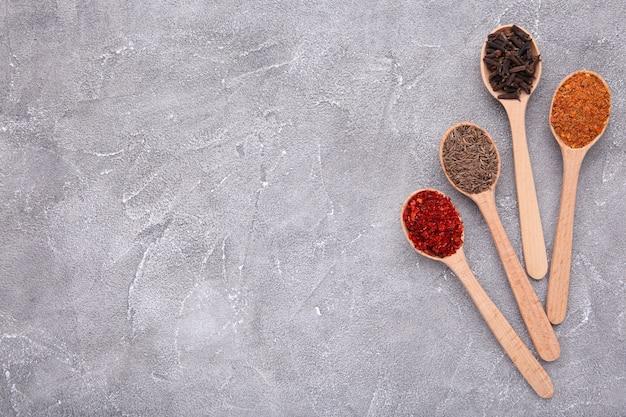 Le spezie si mescolano sui cucchiai di legno su un gray. vista dall'alto