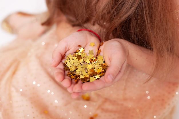 Le stelle dorate brillano sulle mani e sui palmi del bambino. le mani del bambino tengono coriandoli di stelle dorate lucide.