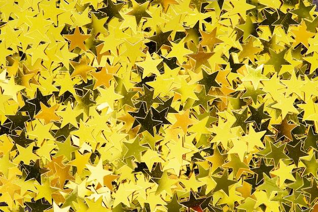 Le stelle dorate lucide scintillano il fondo festivo
