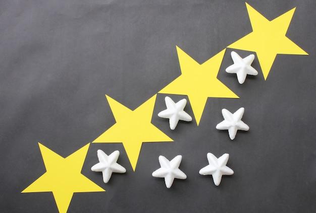 Le stelle gialle e bianche sono posizionate su uno sfondo nero per le idee di business.