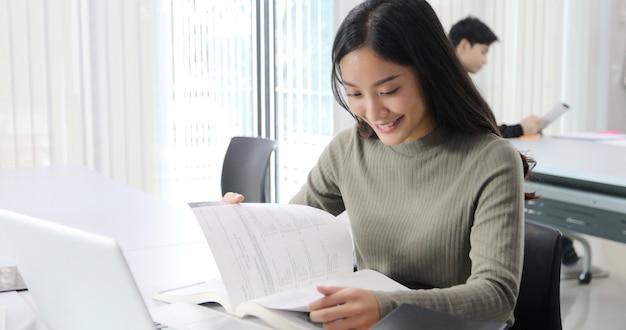 Le studentesse asiatiche sorridono e leggono il libro e stanno usando il taccuino