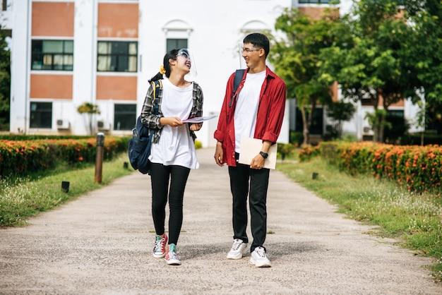 Le studentesse e gli uomini indossano il viso chill e sono in piedi di fronte all'università.
