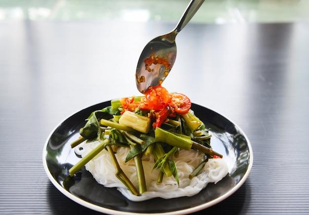 Le tagliatelle di riso tailandesi con la salsa di peperoncini rossi piccanti sono servito sul piatto. vermicelli di riso e verdure in stile asiatico