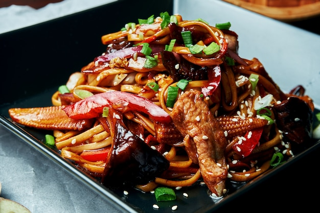 Le tagliatelle di udon con mais, peperone dolce, cipolle, carote e vitello fritti su un wok con salsa teriyaki in banda nera sulla tavola di legno. gustoso cibo di strada asiatico