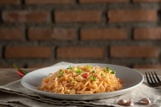Le tagliatelle sono in un piatto bianco rotondo posizionato su un concetto di table.noodle in legno con spazio di copia