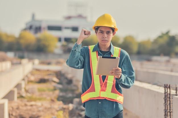 Le tavolette da uomo sono tuta antinfortunistica foreman sicurezza elmetto giallo in cantiere