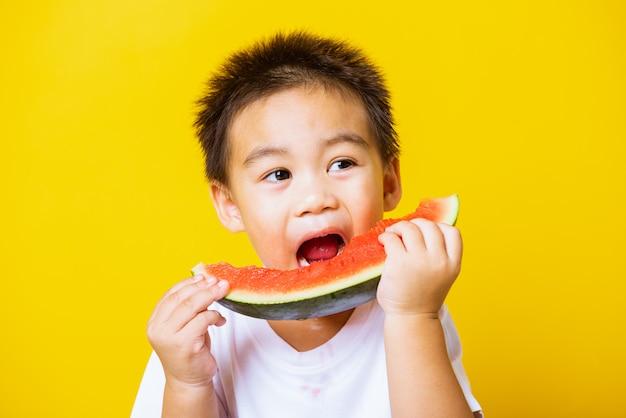 Le tenute asiatiche felici di sorriso del ragazzino del bambino hanno tagliato l'anguria fresca, il concetto sano e l'estate dell'estate