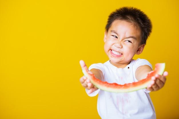 Le tenute asiatiche felici di sorriso del ragazzino del bambino hanno tagliato l'anguria fresca per mangiare