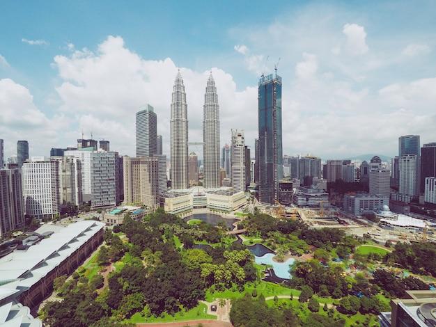 Le torri gemelle di petronas si avvicinano ai grattacieli e agli alberi sotto un cielo blu a kuala lumpur, malesia