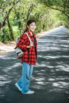 Le turisti donne portano uno zaino e stanno in piedi sulla strada.