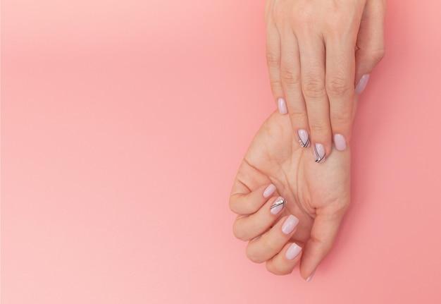 Le unghie della bella donna con la bella manicure alla moda sul rosa