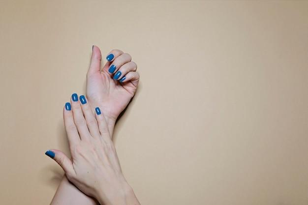 Le unghie della bella donna curata con smalto blu classico sul beige