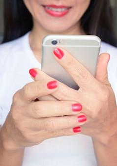 Le unghie rosse colorano le mani che tengono lo smartphone con il fondo sorridente del fronte della donna