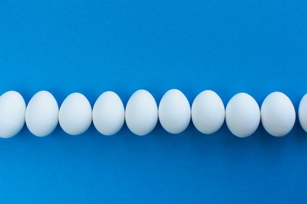 Le uova bianche del pollo sull'azzurro hanno allineato con una linea