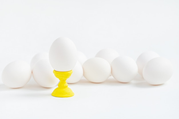 Le uova bianche sui sottobicchieri di legno formano il fondo bianco. prepararsi per le vacanze di pasqua.
