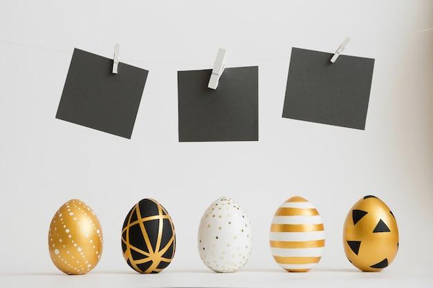 Le uova decorate dorate di pasqua stanno in fila con adesivi di testo nero