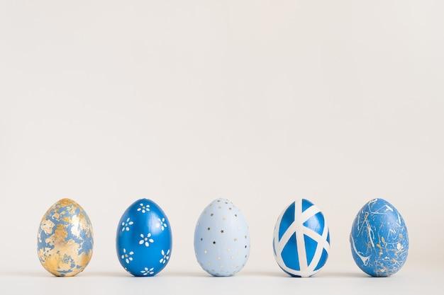 Le uova decorate dorate di pasqua stanno in fila su superficie blu. minimo concetto di pasqua.