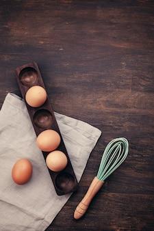 Le uova del pollo di brown nell'uovo di legno controllano i precedenti rustici