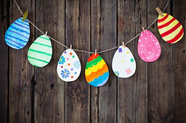 Le uova di carta dipinte a pasqua dipinte appendono su mollette su backgr