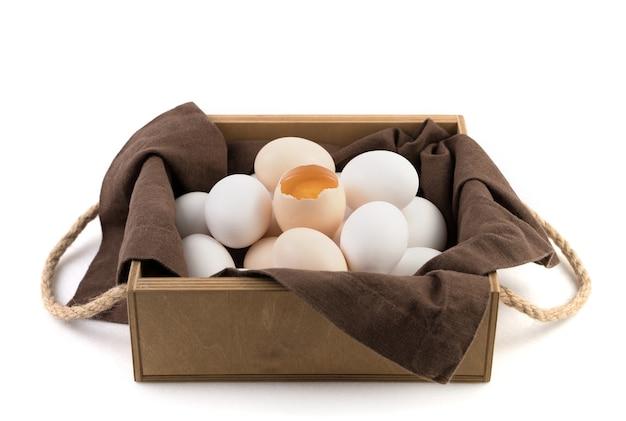 Le uova di gallina fresche sono bianche e marroni con un uovo rotto al centro dove è visibile il tuorlo fresco.