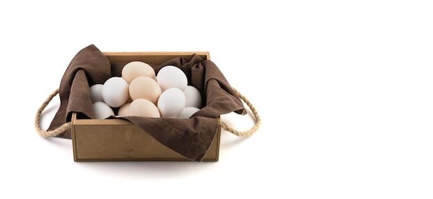 Le uova di gallina sono bianche e marroni in una bella confezione di legno con un tovagliolo di lino marrone.