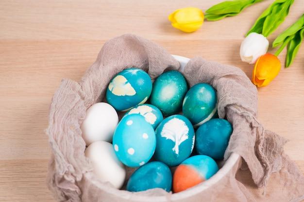 Le uova di pasqua blu organiche con le uova di colore bianco aspettano per dipingere