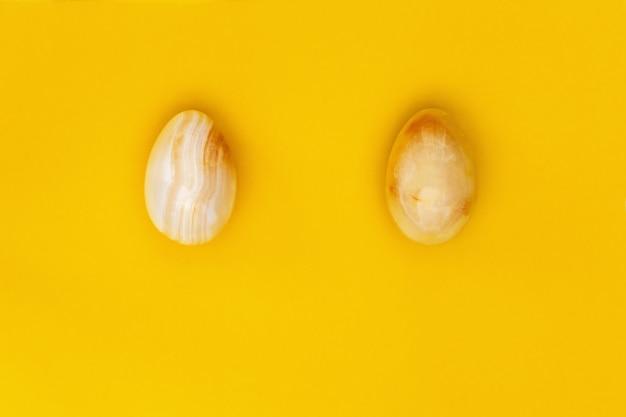 Le uova di pasqua di pietra gialle si chiudono su. composizione in stile minimal con il concetto di design di pasqua. colori pastello e carta vista dall'alto.