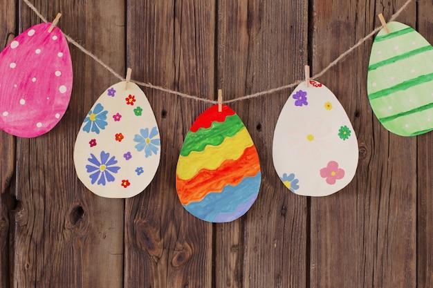Le uova di pasqua dipinte di carta dipinte appendono sulle mollette da bucato sulla vecchia parete di legno del fondo.