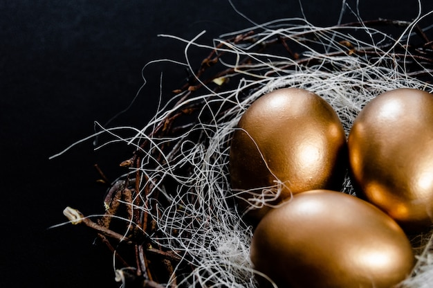 Le uova di pasqua dorate in uccelli annidano su fondo nero. vista superiore del copyspace dell'estratto di concetto di festa di pasqua parecchi oggetti. vista da vicino