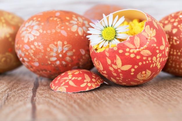 Le uova di pasqua e la margherita fioriscono sulla tavola di legno