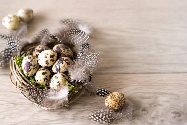 Le uova di pasqua e la piuma delle quaglie in uccello annidano su fondo di legno rustico con lo spazio della copia.