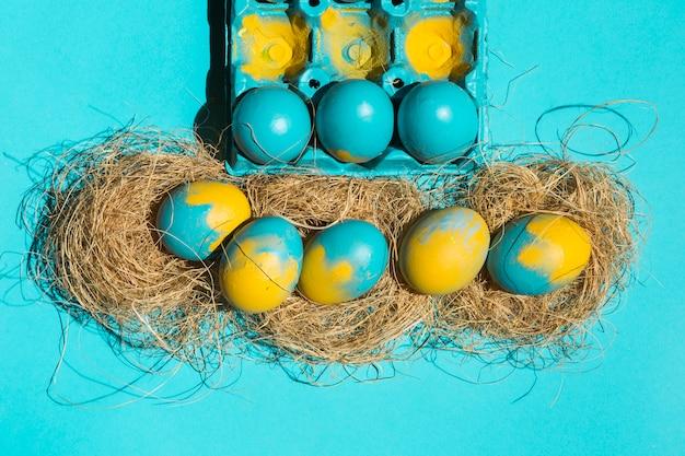 Le uova di pasqua in nidi si avvicinano alla cremagliera sulla tavola