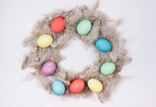 Le uova di pasqua in piuma annidano sulla tavola