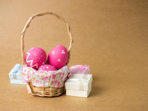 Le uova di pasqua in un canestro tessono il legno sull'angolo sinistro su marrone