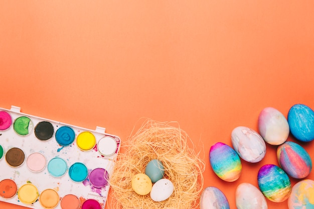 Le uova di pasqua variopinte annidano e tavolozza di plastica con colore di acqua su un fondo arancio