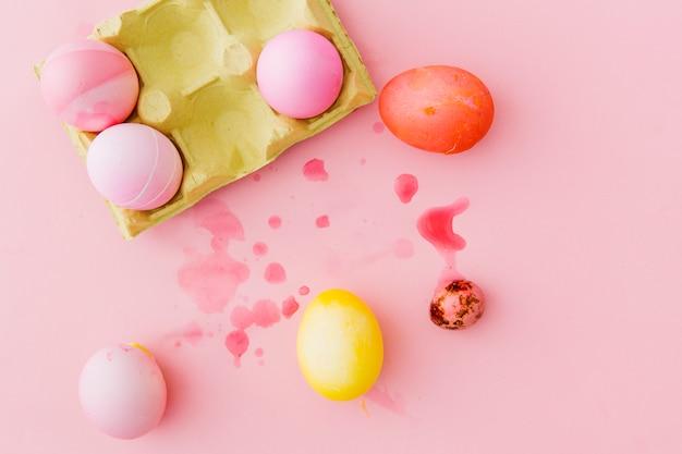 Le uova di pasqua variopinte in contenitore fra spruzza di liquido della tintura