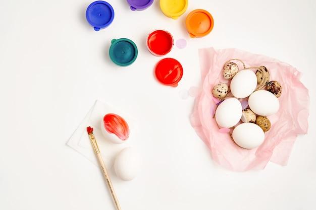 Le uova di quaglie e del pollo annidano e dipingono sul concetto felice del mestiere di pasqua del fondo bianco