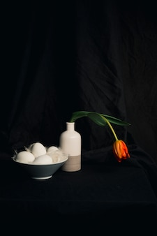 Le uova e le piume si avvicinano al fiore arancio sbiadito in vaso