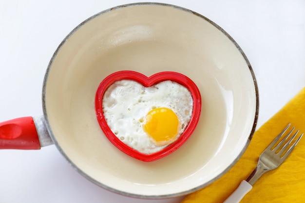 Le uova fritte nel cuore hanno modellato in una padella. concetto di san valentino.