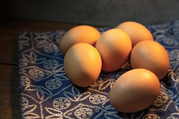 Le uova in ciotola sulla tavola di legno per contenuto alimentare.