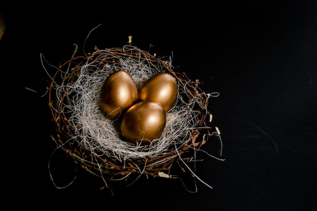 Le uova in uccelli annidano su fondo nero. vacanze di pasqua