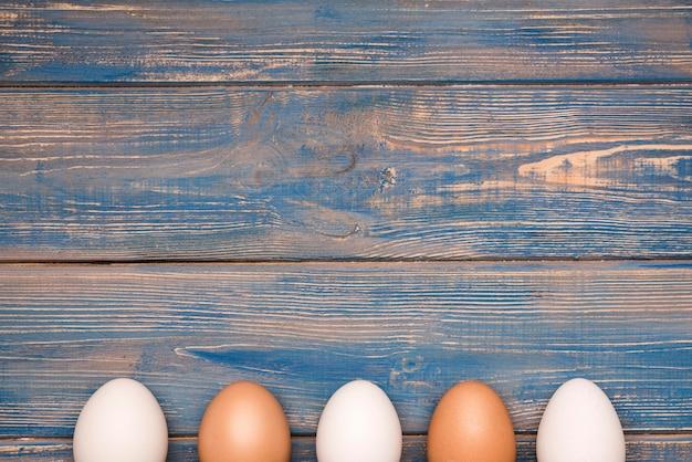Le uova incorniciano su fondo di legno