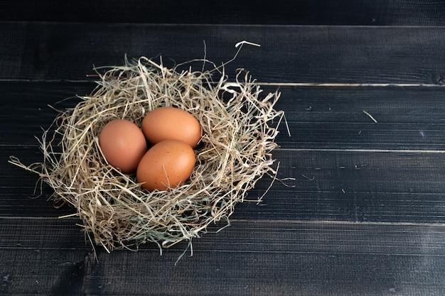 Le uova marroni fresche del pollo in fieno annidano sul nero