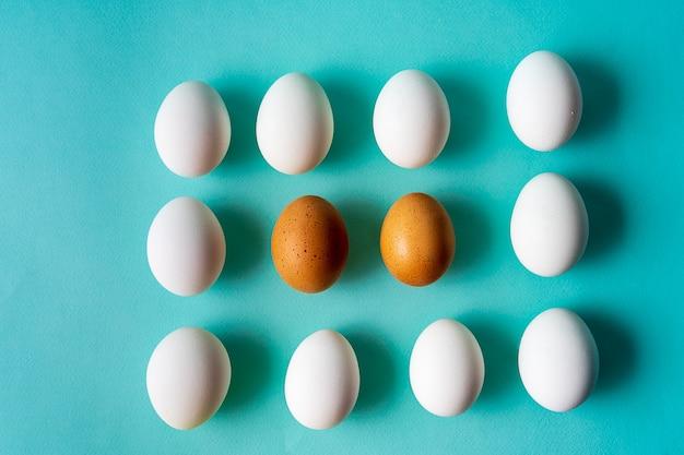 Le uova modellano sopra il fondo pastello dell'acqua.