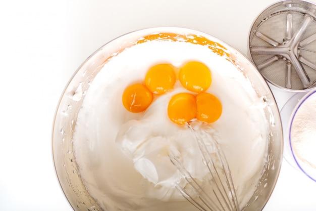 Le uova montate concetto del forno di cottura si mescolano con gli ingredienti per il pan di spagna casalingo su fondo bianco