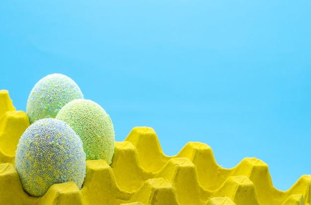 Le uova variopinte decorano con la polvere di spruzzo del gelato per il giorno di pasqua.